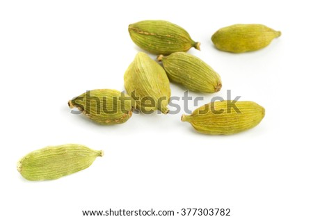 Cardamom seed pods close up with shallow depth of field over white background - stock photo
