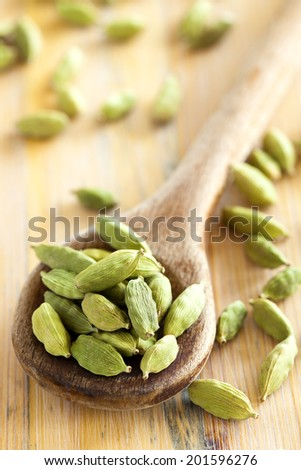 Cardamom seeds in the wooden spoon - stock photo