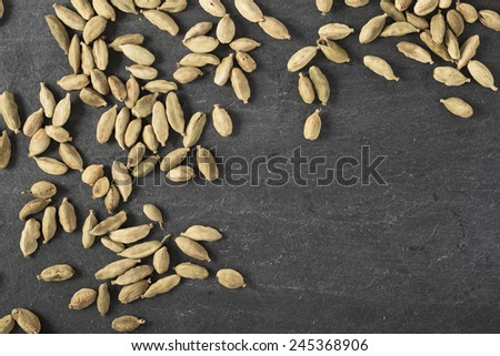 Cardamom seeds spread on slate surface with copy space. - stock photo