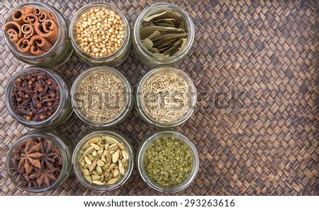Cardamom, star anise, cinnamon, clove, coriander seed spices and dried bay leaves, parsley, thyme, rosemary herbs in mason jars over wicker background - stock photo