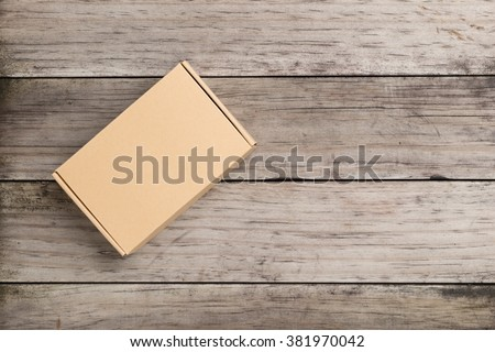 Cardboard box on a  wooden background - stock photo