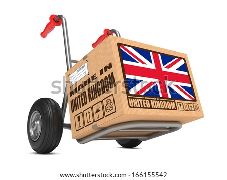 Cardboard Box with Flag of United Kingdom and Made in United Kingdom Slogan on Hand Truck White Background. Free Shipping Concept. - stock photo
