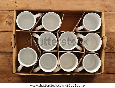 cardboard box with white ceramic coffee cups - stock photo