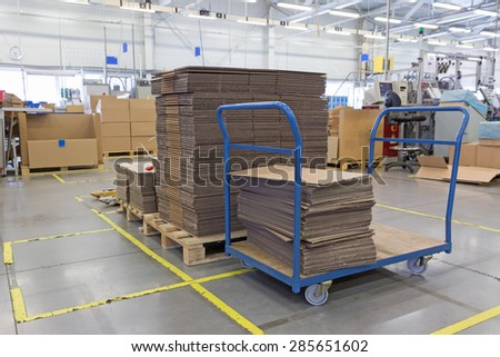 Cardboard boxes are folded in a designated place in the assembly hall. The show of lean management. All potential trademarks are removed. - stock photo