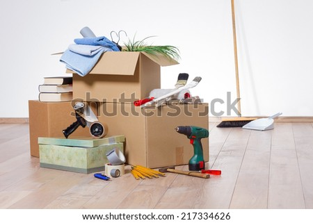 Cardboard boxes with a broom, a shovel and tools on a wooden floor