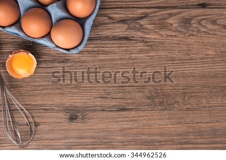 Cardboard egg box and egg beater on wooden table. Top view with copy space - stock photo