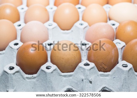 Cardboard egg box and many eggs - stock photo