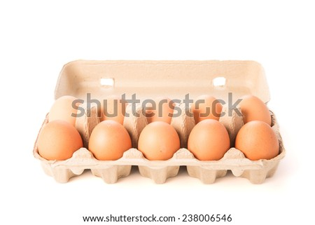 Cardboard egg box with ten brown eggs isolated with clipping path - stock photo