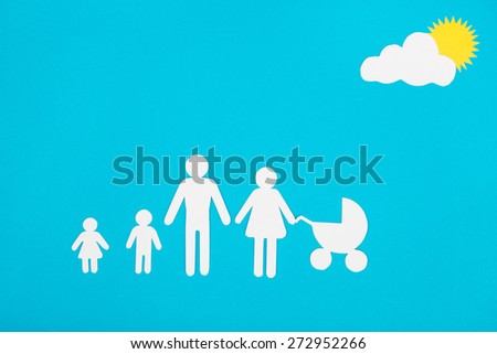 Cardboard figures of the family on a blue background. The symbol of unity and happiness. - stock photo
