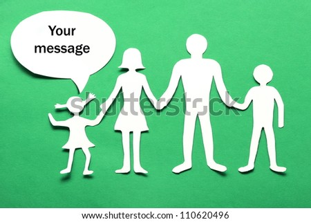 Cardboard figures of the family on a green background. The symbol of unity and happiness. Above the daughter bubble, which you can enter your message. - stock photo