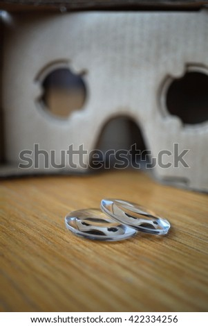 Cardboard goggles headset used for virtual reality with separated glass lenses  - stock photo