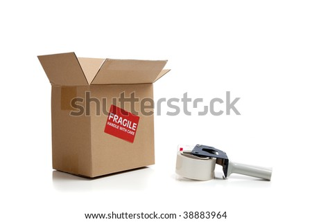 Cardboard shipping box with a tape gun on a white background - stock photo