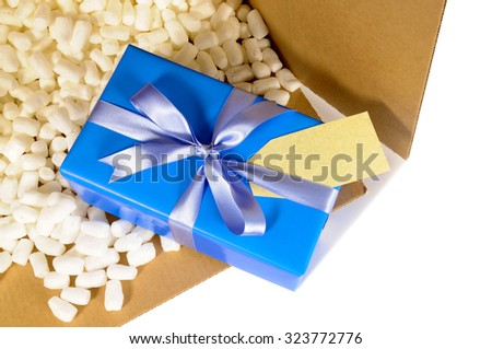 Cardboard shipping delivery box with one unique blue Christmas gift inside and polystyrene packing pieces.  Top view. - stock photo