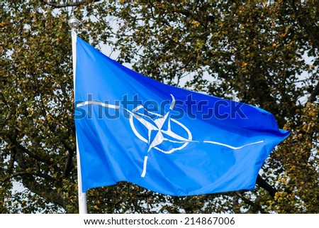 CARDIFF, WALES - SEPTEMBER 3 2014: The NATO flag flies over the ramparts of Cardiff Castle in preparation for the NATO summit.  Security is very tight due to the threat of disruptive protests