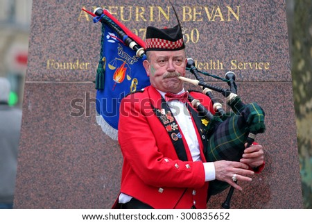 CARDIFF, WALES, UNITED KINGDOM, MArch 14th, 2015, Scottish man playing bagpipe in front of Aneurin Bevan statue from Cardiff city center, after a rugby mach between Wales and Ireland.  - stock photo