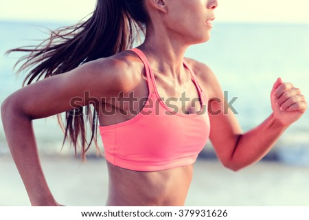 Cardio running workout - Upper body closeup crop of unrecognizable woman runner in fast motion showing pink sports bra activewear clothing in ocean beach nature background. - stock photo