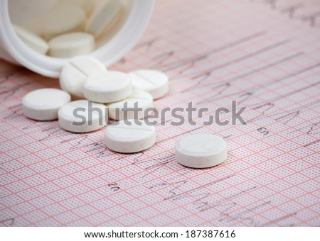 Cardiogram and spilled white tablets.Medical concept - stock photo