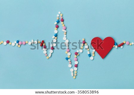 Cardiogram is made of colorful drug pills and red paper heart, pharmaceutical and cardiology concept - stock photo