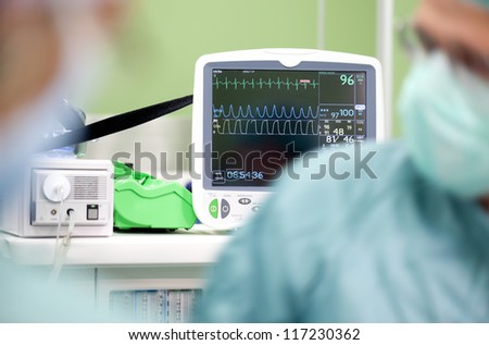 Cardiogram monitor in surgery while not recognizable doctor operates, focus on screen