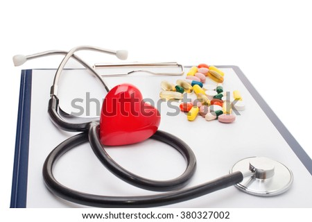 Cardiogram with red heart and tablets, closeup - stock photo