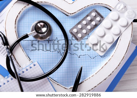 Cardiogram with stethoscope and pills on table, closeup - stock photo