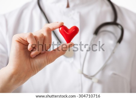 Cardiologist holding a ceramic red heart, closeup shot - stock photo