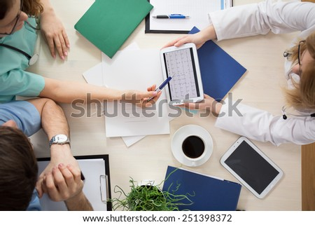 Cardiologists using digital tablet during medical meeting - stock photo