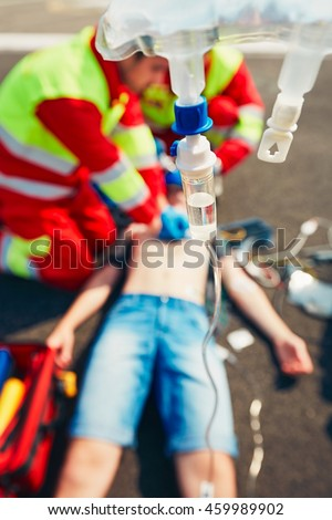 Cardiopulmonary resuscitation. Rescue team (doctor and a paramedic) resuscitating the man on the street. - selective focus on the drop