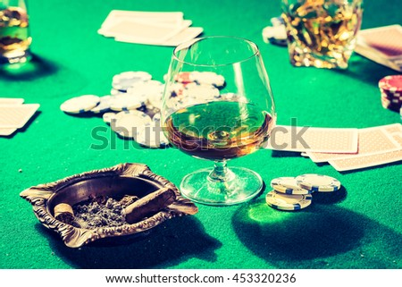 Cards and chips in old gambling table - stock photo