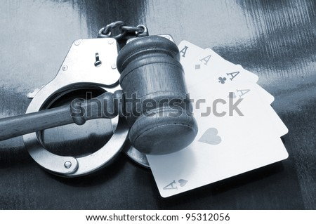 Cards, handcuffs and gavel on wooden table - stock photo