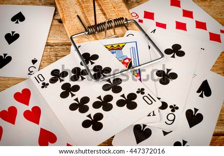 Cards inside a mousetrap, a gambling addiction concept