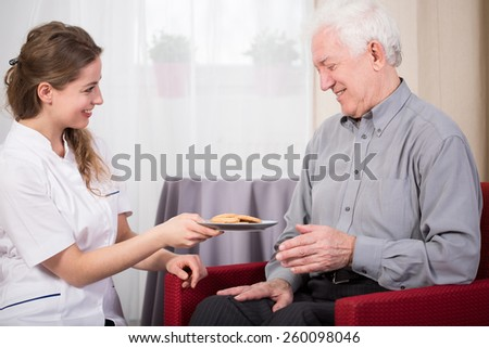 Care assistant and retired man at home - stock photo