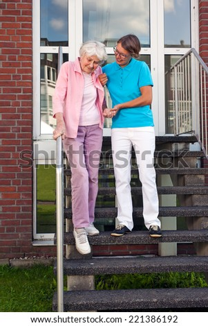 Care assistant helping a senior lady on steps holding her hand as they descend a set of wooden stairs outdoors on the care home. - stock photo