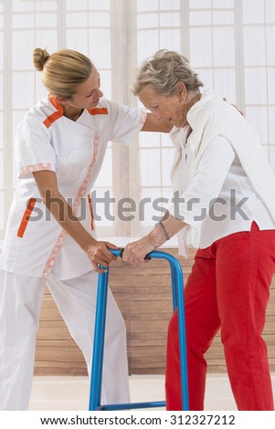 Care giver helping elderly woman to walk with a walker - stock photo