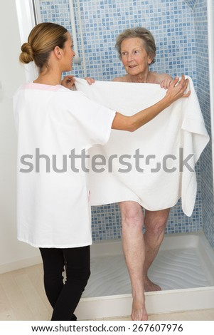 Care giver or nurse  assisting elderly woman for shower - stock photo