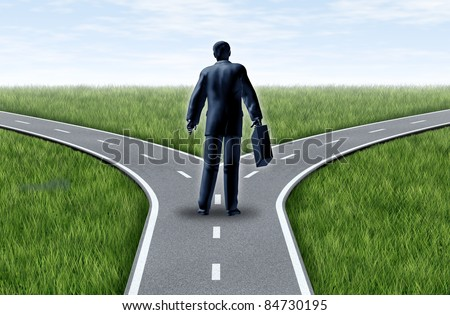Career decision for a business man at a cross roads showing a fork in the road representing the concept of a work dilemma choosing the direction to go when facing two equal or similar job options. - stock photo