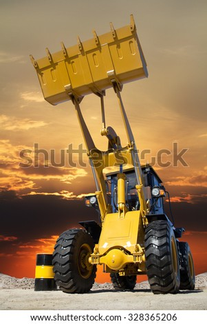 Career in the tractor, the tractor at sunset, tractor with big bucket on the sand, transport of building materials, a barrel of fuel and tractors, mining in the quarry, heavy industry. - stock photo
