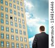 Career opportunity. Businessman facing company building, looking at open office window. - stock photo