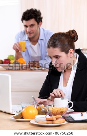 Career woman eating breakfast while working - stock photo