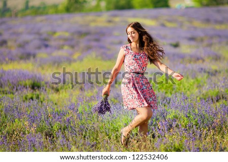 Carefree adorable girl with bouquet in fairy field of lavender. Summer freedom enjoy concept - stock photo