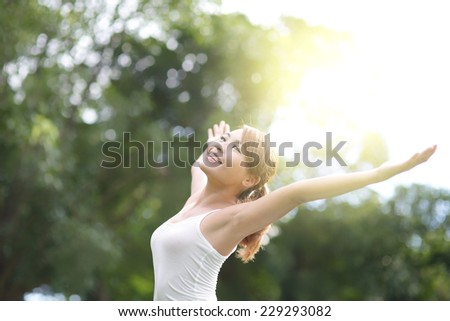 Carefree and free cheering woman in the park. girl raising her arms up smiling happy. asian beauty - stock photo