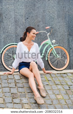 Carefree and stylish. Attractive young smiling woman sitting at the roadside and near her vintage bicycle  - stock photo