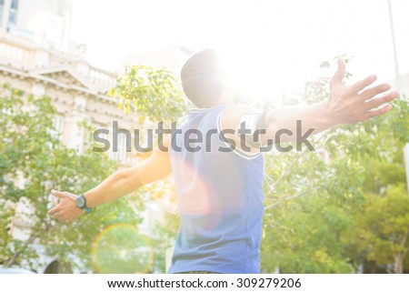 Carefree athlete with arms outstretched in the city - stock photo