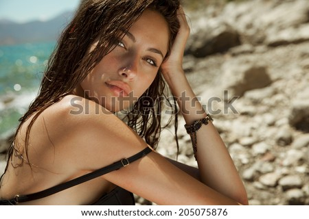 Carefree beautiful brunette with wet look & long hair on the beach. Natural woman beauty. Toned in warm colors. Copy space for your text. horizontal shot, outdoors - stock photo