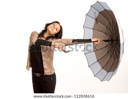 Carefree beautiful trendy young woman twirling an umbrella holding it out to the side at arms length isolated on white - stock photo