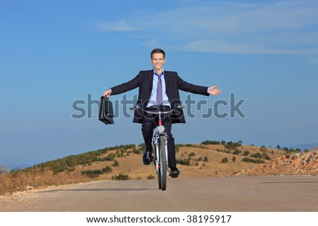 Carefree businessman holding a  briefcase and riding a bicycle outdoors - stock photo