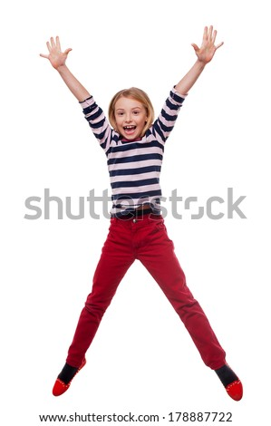 Carefree child. Full length of happy little girl jumping while standing isolated on white - stock photo