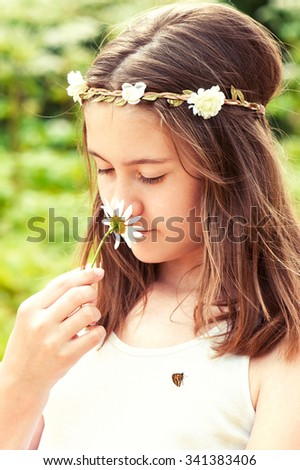 Carefree childhood. Happy boho style cheerful girl with floral headband on head and butterfly smelling camomile. Summertime multicolored outdoors vertical image. - stock photo