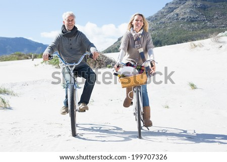 Carefree couple going for a bike ride and picnic on the beach on a bright but cool day - stock photo