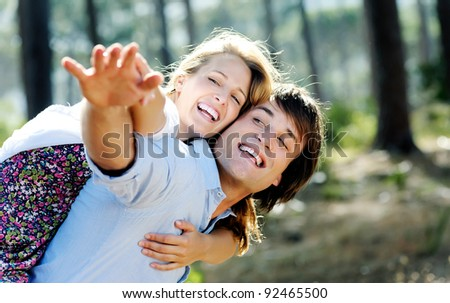 carefree couple have fun embracing and playing outdoors in the sunlight. a real couple, real emotions, real love. - stock photo